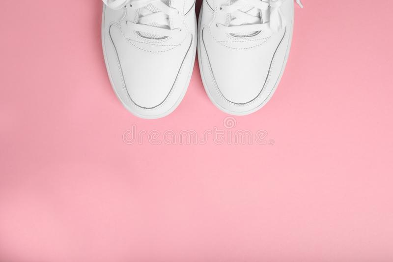 Stylish summer white running shoes on a pink background, top view. Flat lay with copy space for text stock image