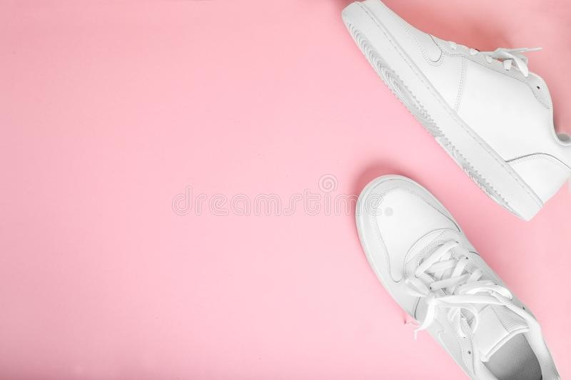 Stylish summer white running shoes on a pink background, top view. Flat lay with copy space for text stock images