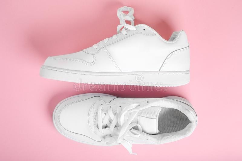 Stylish summer white running shoes on a pink background, top view. Flat lay stock photography