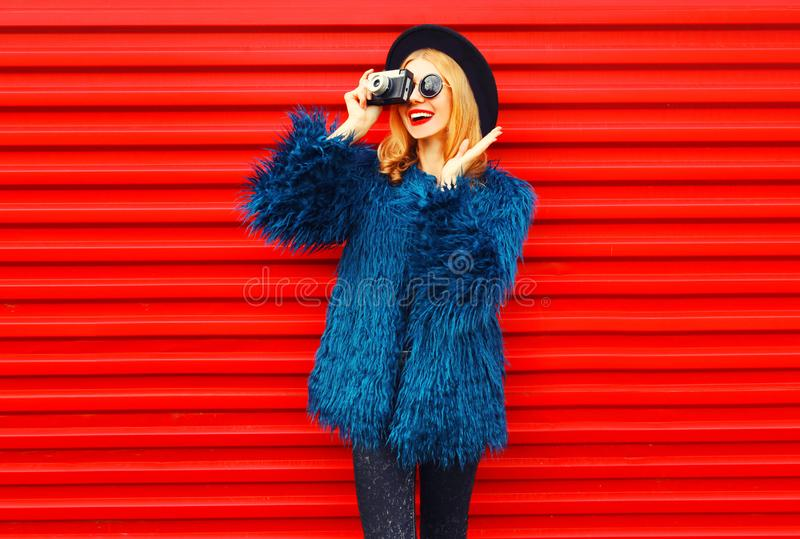 Stylish surprised woman with retro camera taking picture wearing blue faux fur coat, round hat and sunglasses over colorful red stock images