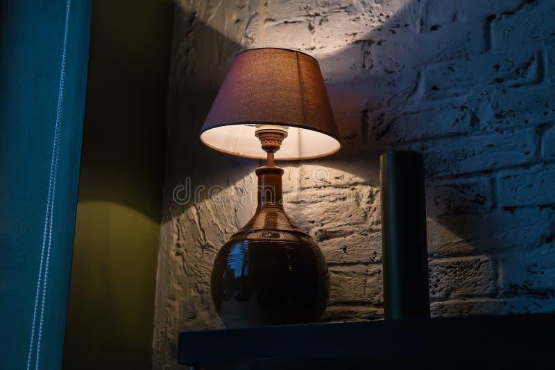 Stylish table lamp illuminating a brick wall royalty free stock images