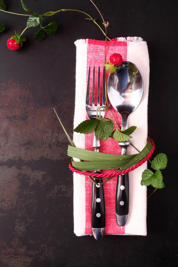 Stylish table setting with red cord and leaves. Stylish table setting with red cord and trailing leaves with a wild strawberry tied around a spoon and fork on a stock image