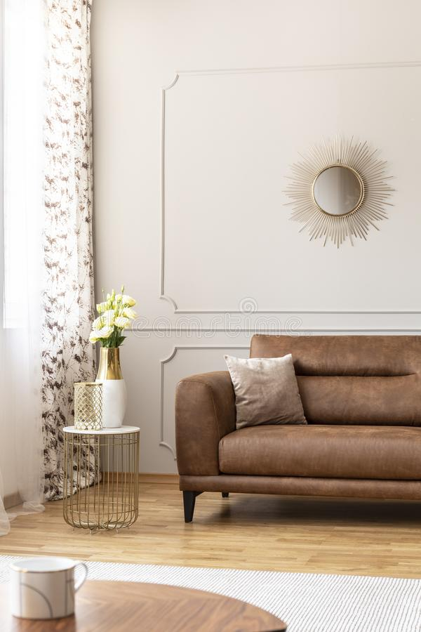 Stylish table with vase with flowers on it next to comfortable leather couch with beige pillow in luxury living room interior. Real photo royalty free stock photo