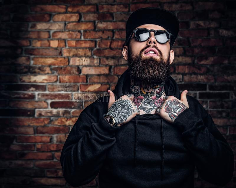 A stylish tattooed guy in a black hoodie and sunglasses. Studio photo against brick wall royalty free stock photo