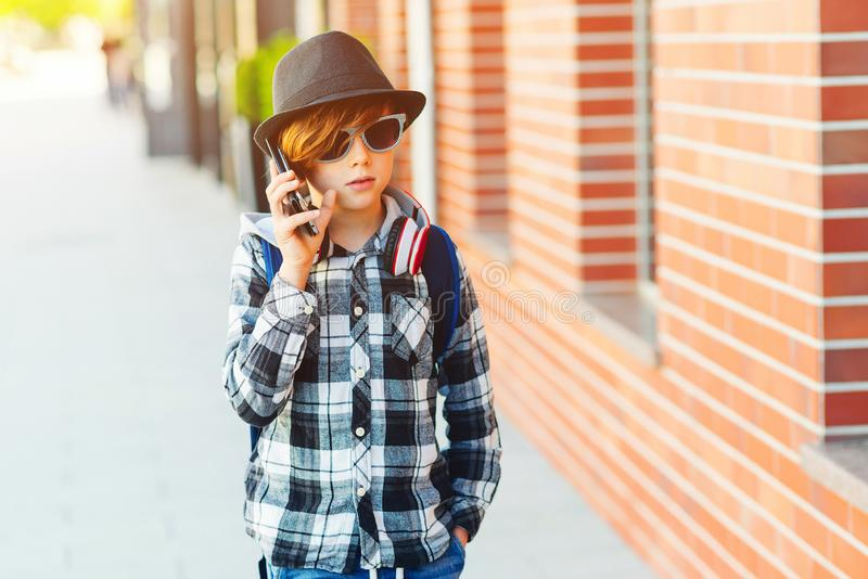 Stylish teenage boy with mobile phone. Hipster kid in sunglasses and modern hat at city street. Young boy talking on the royalty free stock images