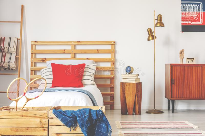 Stylish teenager bedroom interior with wooden bed and vintage furniture, real photo. Concept royalty free stock image
