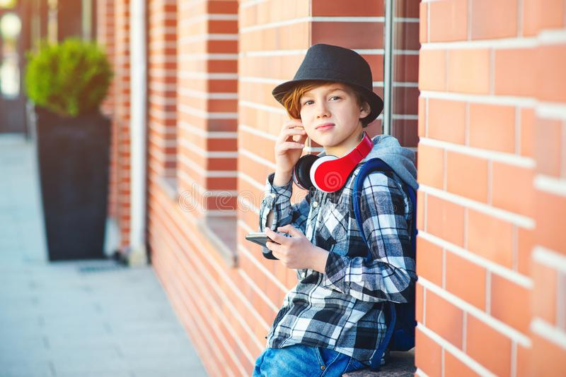 Stylish teenager boy with headphones and mobile phone outdoors. Cute boy with headphones listens to the music. Schoolboy plays. Games on smartphone. Fashion stock images