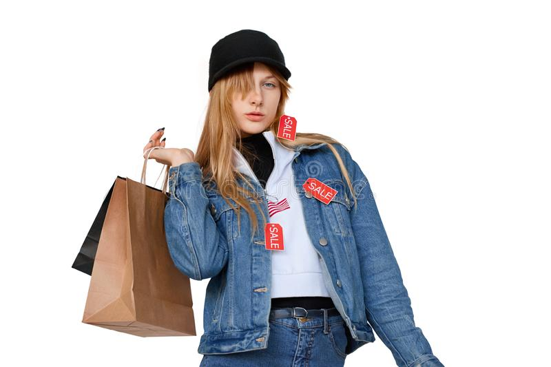 Stylish teenager girl with shopping bags and sales labels on denim wear royalty free stock photo