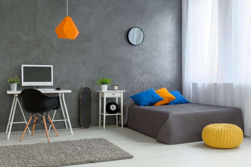 Stylish teenager's room. Stylish designed boy teenager's bedroom with grey walls and white furniture and colorful decorations stock photography