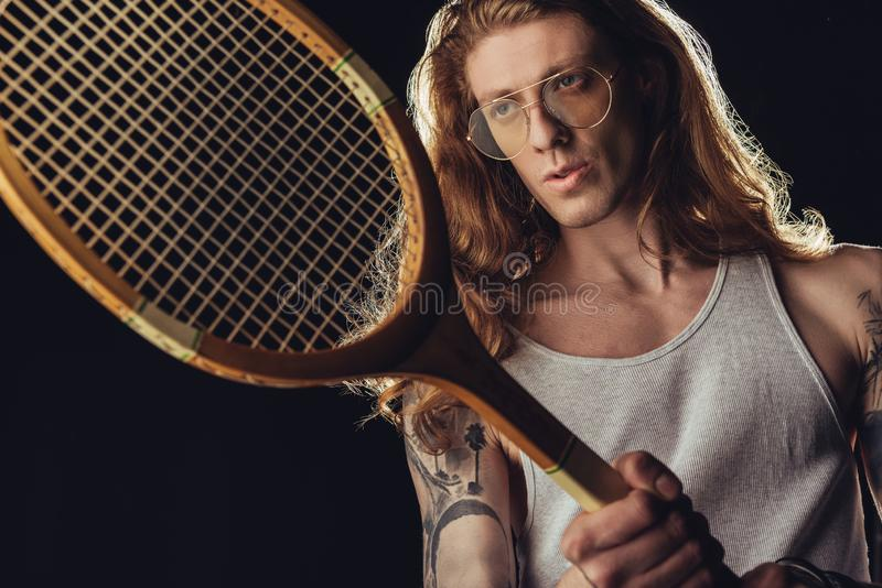 Stylish tennis player with vintage wooden racket. Isolated on black royalty free stock photo