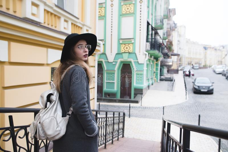 Stylish tourist girl walking in the beautiful old town and looking into the camera. royalty free stock photos