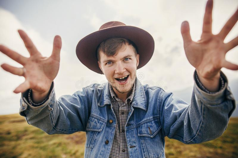 Stylish traveler excited man in hat having fun on top of sunny m royalty free stock photography