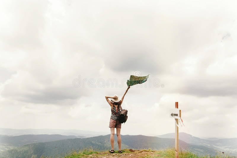 Stylish traveler hipster woman with backpack holding map into s stock photo