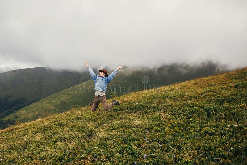 Stylish traveler man in hat jumping on top of mountains with clouds. space for text. hipster guy traveling, funny emotions. Amazing atmospheric moment. travel royalty free stock photo