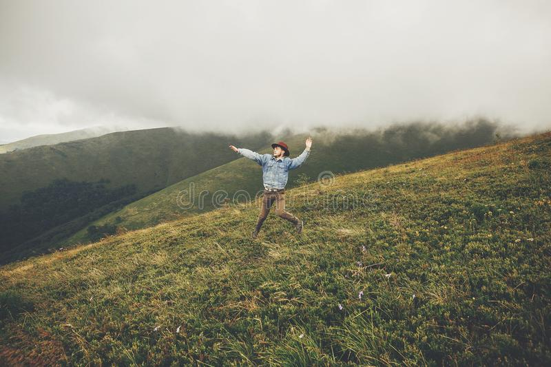 Stylish traveler man in hat jumping on top of mountains with clouds. space for text. hipster guy traveling, funny emotions. Amazing atmospheric moment. travel royalty free stock photography