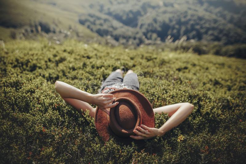 Stylish traveler woman in hat lying on grass and relaxing in mountains. hipster girl on top of mountain, resting, hat on her face. Space for text. atmospheric stock image
