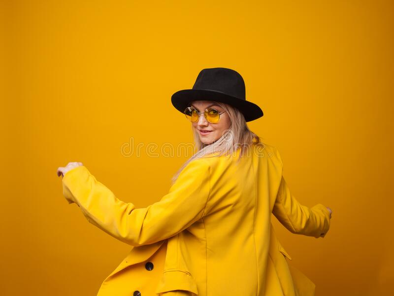 Stylish trending young woman in bright clothes on yellow background, copy space. Cool blonde royalty free stock photos