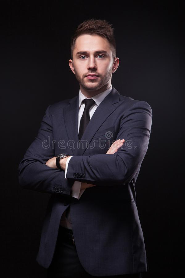 Stylish, trendy businessman in a business suit on a black backgr. Ound is confidently looking into the camera stock image