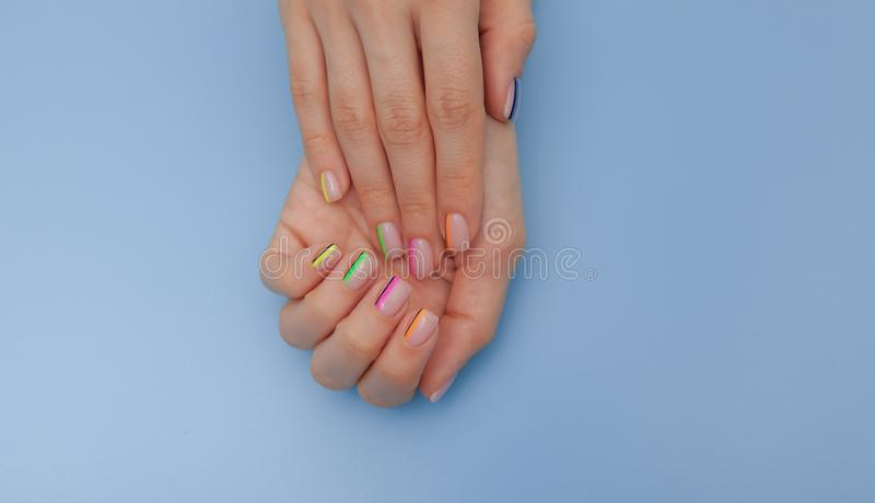Stylish trendy female manicure. Beautiful young woman`s hands on blue background stock images