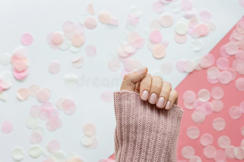 Stylish trendy female pink manicure. Beautiful young woman hand on pink and white background with flowers and place for text. stock photography
