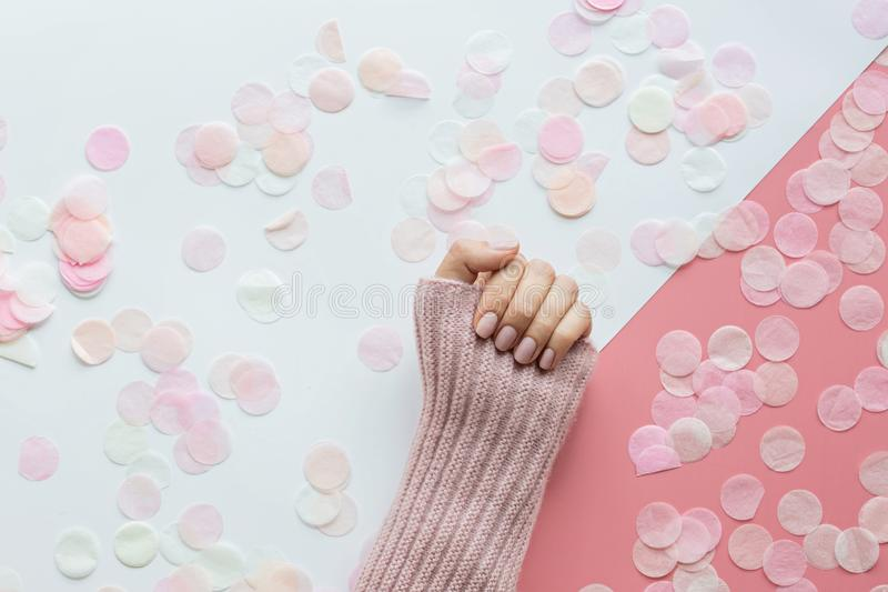 Stylish trendy female pink manicure. Beautiful young woman hand on pink and white background with flowers and place for text. stock image