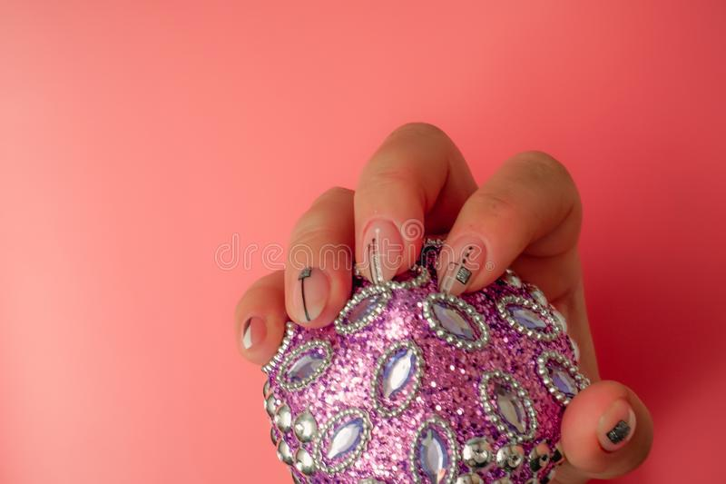 Stylish trendy female pink manicure. Pink manicure with with black geometric pattern on almond-shaped nails on a pink background.  royalty free stock photography