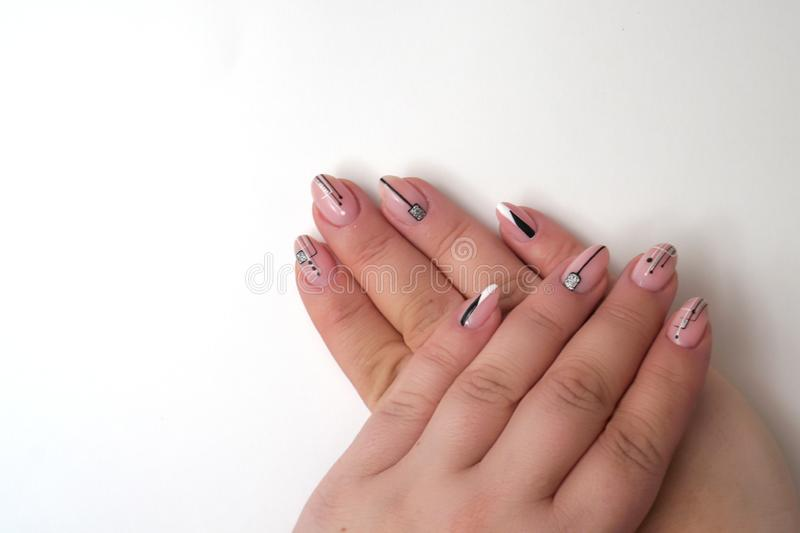 Stylish trendy female pink manicure. Pink manicure with with black geometric pattern on almond-shaped nails  Isolated on a white. Background stock images