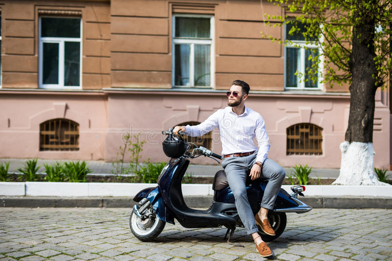 Stylish trendy man wearing modern sunglasses and a formal suit sitting waiting on a motorcycle on city street stock photography