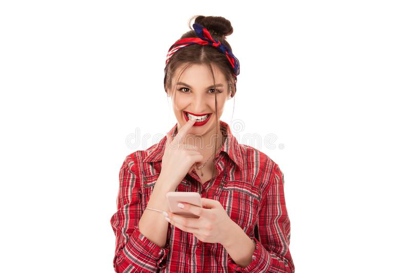 Flirting woman holding phone in hands. Stylish trendy nice cute cheerful adorable lovely attractive brunette caucasian girl with bow in hair in casual red royalty free stock photography