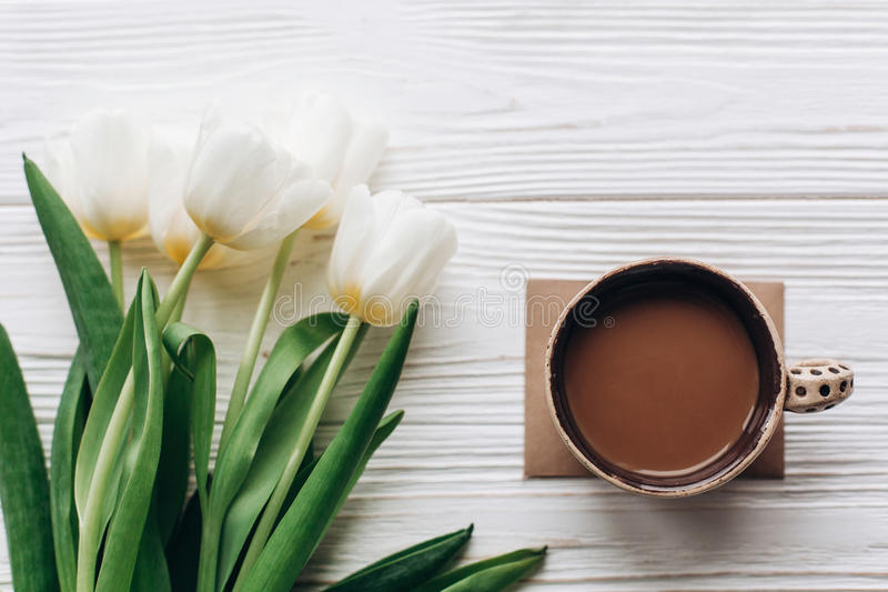 stylish tulips and morning coffee on white wooden rustic background. flat lay with flowers with space for text. hello spring royalty free stock photo