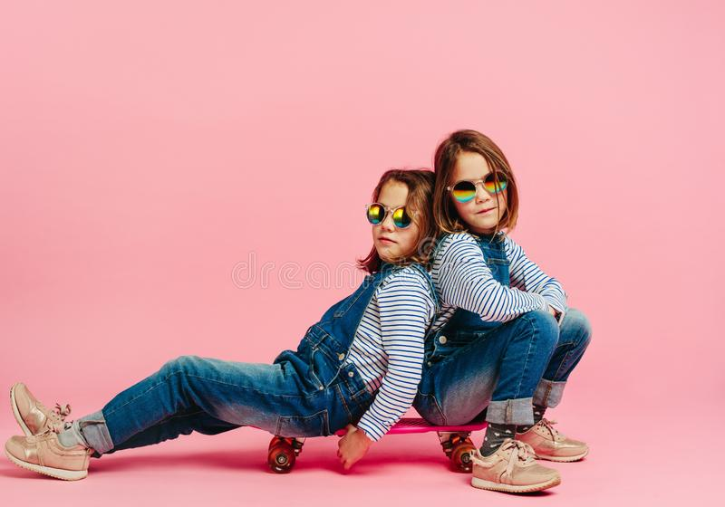 Stylish twin girls sitting together on a skateboard stock photo