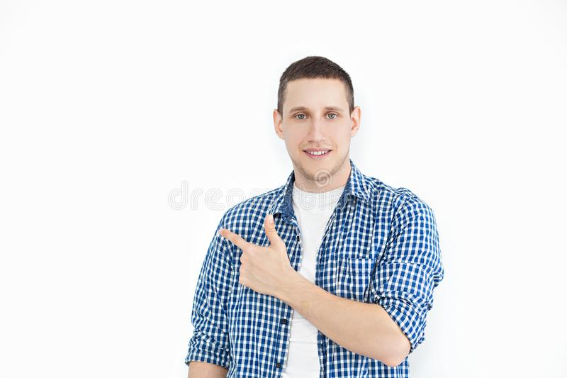A stylish unshaven man in a shirt points to a copy of the space on a white wall, as something nice shows, has a smiling look, adve stock images