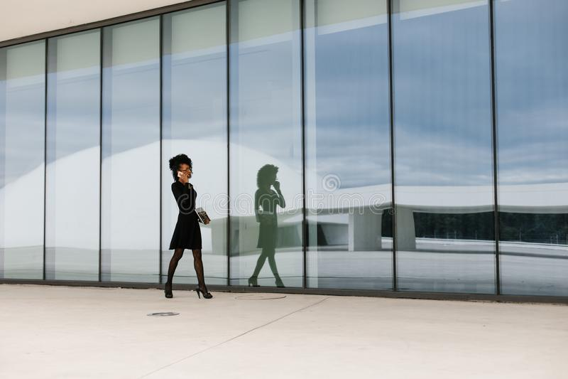 Professional woman walking and talking on cellphone outside. royalty free stock image
