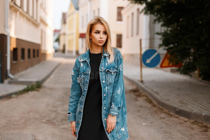 Stylish urban pretty young woman in a black stylish dress in a fashionable long denim jacket posing in a city on the street stock images