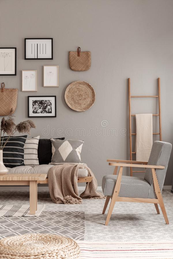 Stylish vintage armchair in contemporary living room interior with futon settee and wooden scandinavian ladder with blanket. Stylish vintage armchair in royalty free stock image