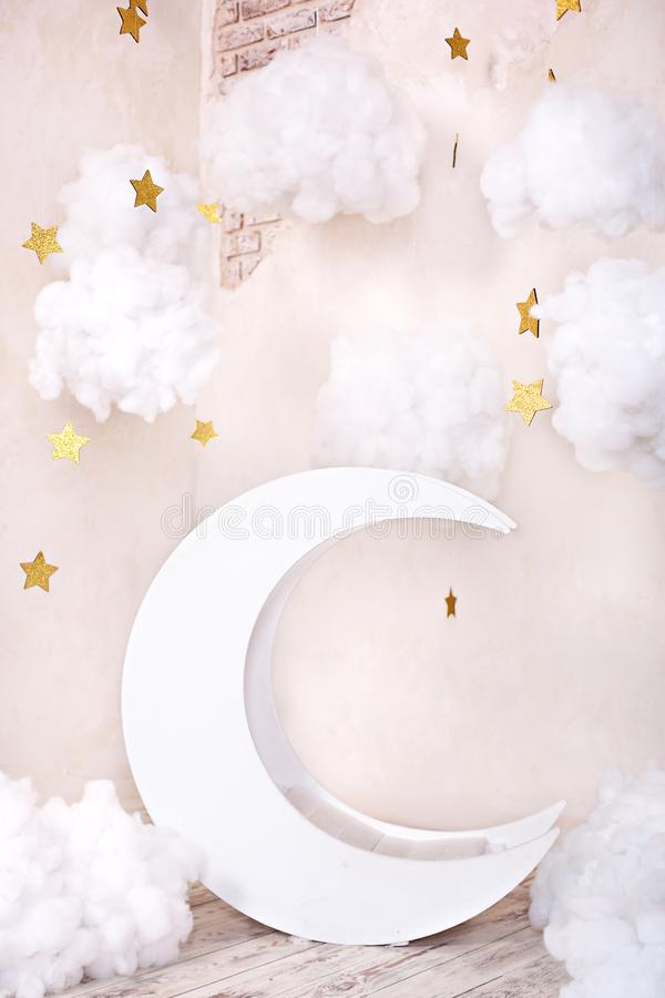 Stylish vintage children`s room with a wooden moon and textile clouds. Children location for a photo shoot. Moon with stars and cl. Stylish vintage children`s stock images