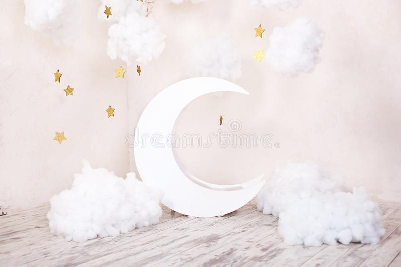 Stylish vintage children`s room with a wooden moon and textile clouds. Children location for a photo shoot. Moon with stars and cl. Stylish vintage children`s royalty free stock photos