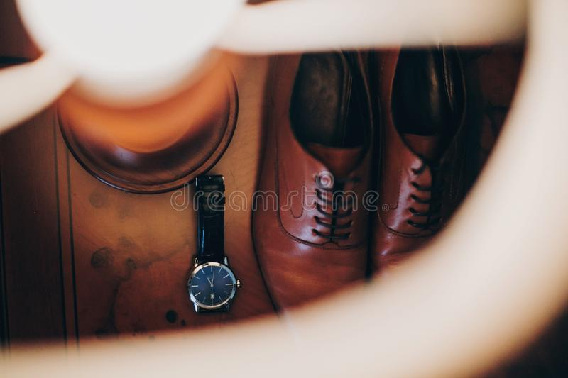 Stylish watch and expensive brown shoes for groom on wooden table in hotel room. Morning preparation before wedding ceremony. Men stock images