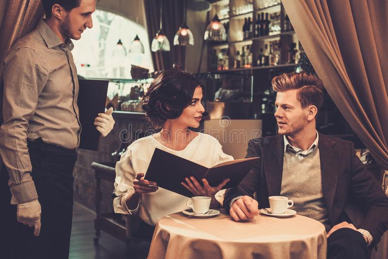 Stylish wealthy couple with menu royalty free stock photography