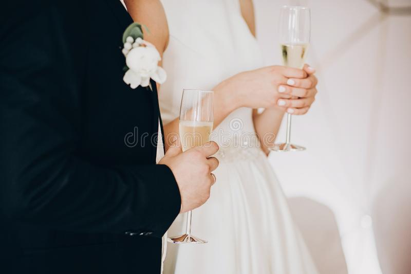Stylish wedding couple holding champagne glasses and toasting at wedding reception in restaurant, cropped view. Bride and groom stock photography