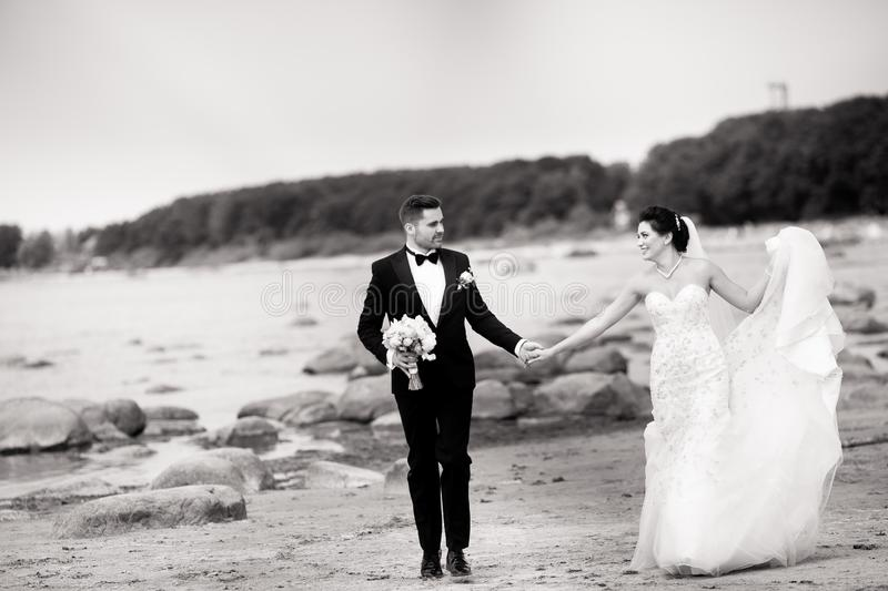 Stylish wedding couple standing on sea shore. Newlyweds are walking by the sea. Black and white stock image