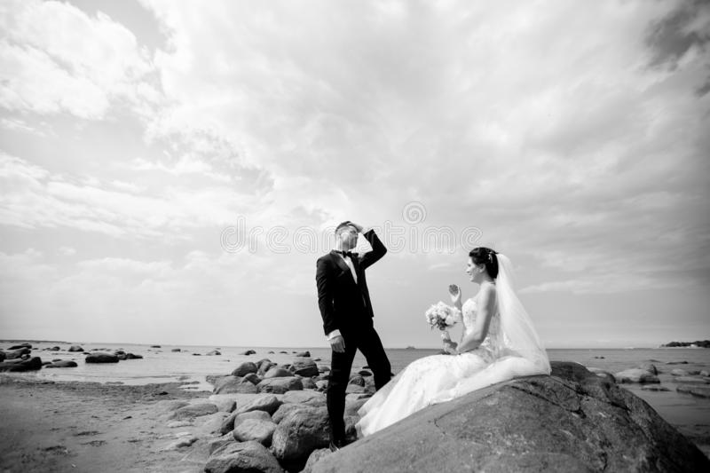 Stylish wedding couple standing on sea shore. Newlyweds are walking by the sea. Black and white royalty free stock photography