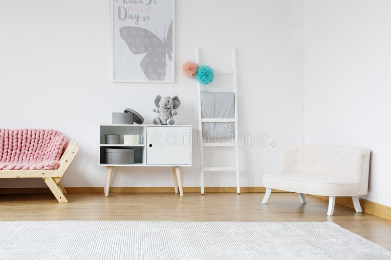 Designed pastel room. Stylish white settee for kids with grey poster on white wall in designed pastel room stock image