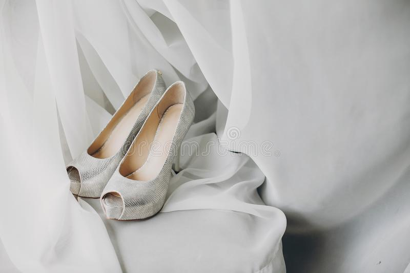 Stylish white shoes for bride on white tulle in soft morning light in hotel room. Morning preparation before wedding ceremony. stock photography
