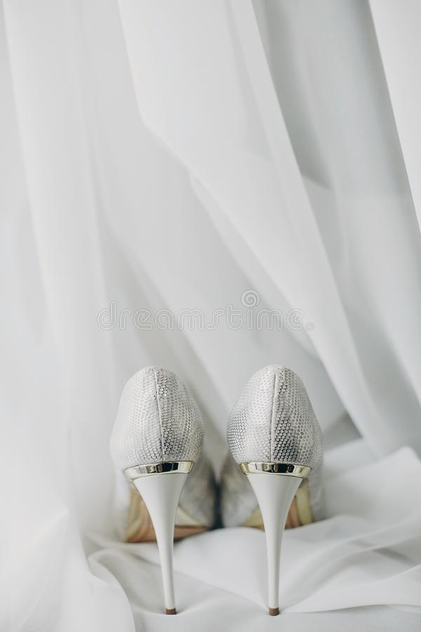 Stylish white shoes for bride on white tulle in soft morning light in hotel room. Morning preparation before wedding ceremony. stock images