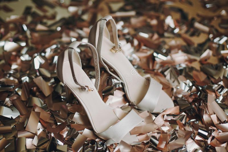 Stylish white shoes with high heels on gold and silver confetti,bridal boudoir morning details before wedding ceremony. Hen shower royalty free stock images
