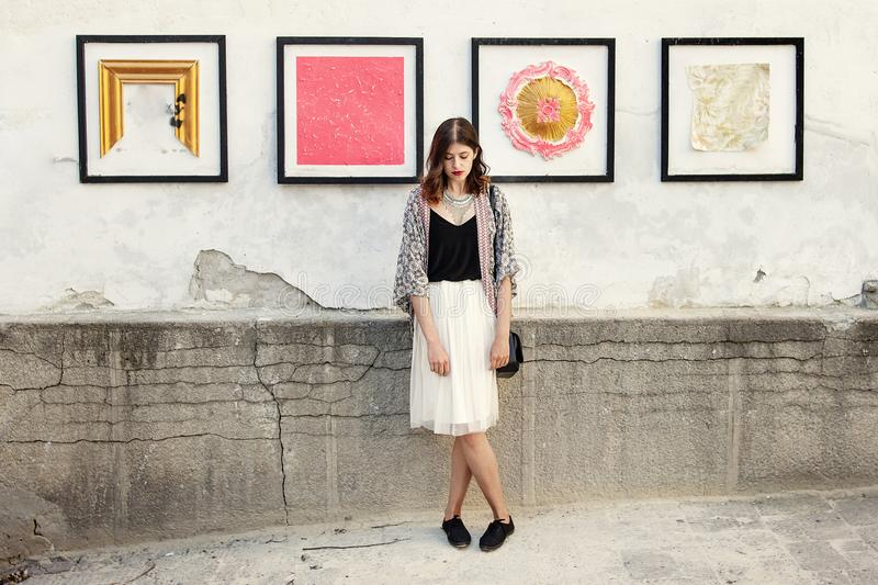 Stylish woman with boho outfit posing at wall with street art in. European city royalty free stock images