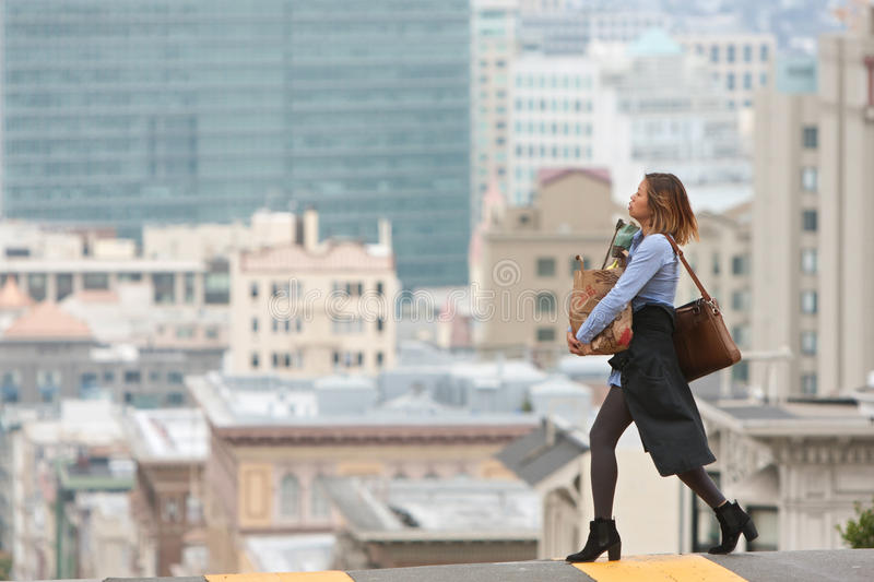 Stylish Woman Carrying Groceries Crosses Scenic San Francisco Street royalty free stock photo