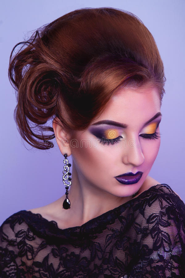 Stylish woman with creative hairstyle and make up in studio. On magenta background stock image