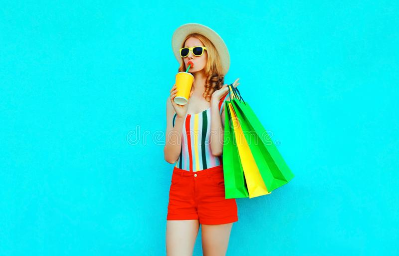 Stylish woman drinking juice holding shopping bags in colorful t-shirt, summer straw hat, sunglasses, red shorts on blue royalty free stock photo